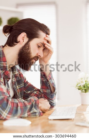 Hipster businessman stressed at his desk in his office - stock photo