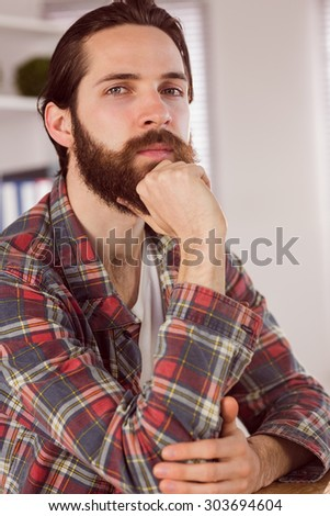 Hipster businessman thinking at his desk in his office - stock photo
