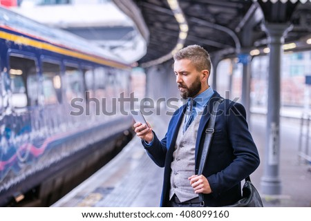 Hipster businessman with smartphone, waiting at the train platfo - stock photo