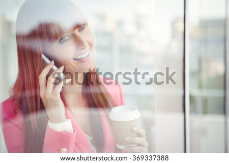 Hipster businesswoman having a phone call in office - stock photo