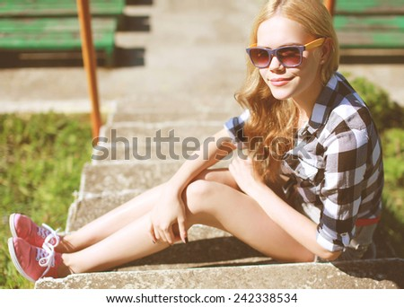 Hipster cool girl in sunglasses outdoors resting in the city park summer - stock photo