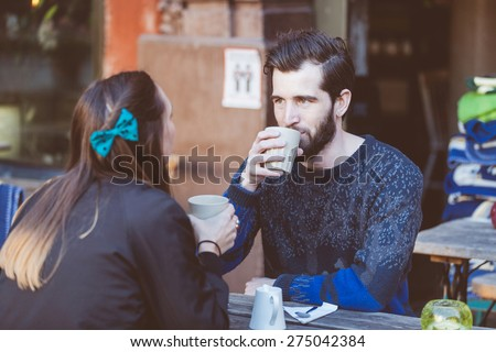 Hipster couple drinking coffee in Stockholm old town. They're sitting face to face. The man is wearing a blue sweater and the woman a striped shirt with black leather jacket. - stock photo
