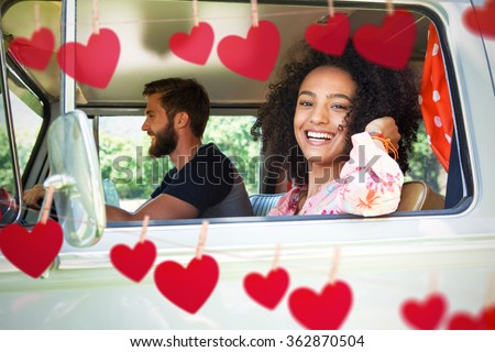 Hipster couple driving in camper van against hearts hanging on a line - stock photo