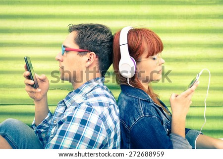 Hipster couple in disinterest moment with mobile phones - Concept of apathy sadness and isolation using new technologies - Boyfriend and girlfriend with smartphones addiction - Vintage filtered look