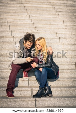 Hipster couple in love having fun with smartphone - Modern concept of connection in a relationship together with mobile phone technology - City urban lifestyle representing everyday life rapport - stock photo
