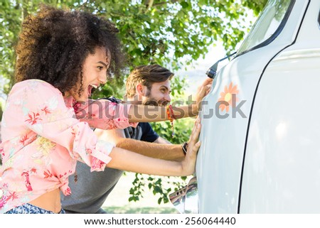 Hipster couple pushing camper van on a summers day - stock photo