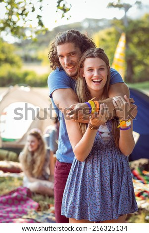Hipster couple smiling at camera at a music festival - stock photo
