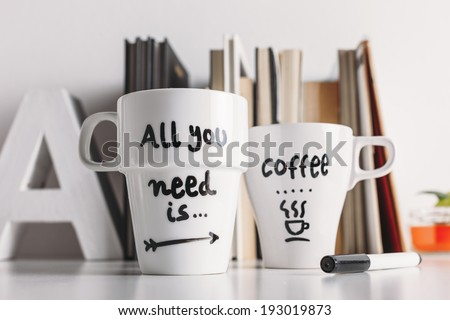 Hipster cup of coffee on a books library./ Close up of two white coffee mug with diy decoration.