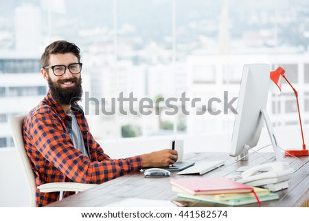 Hipster drawing on graphic tablet in the office - stock photo