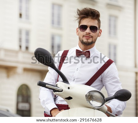 Hipster fashion men with scooter on a sunny day in the city - stock photo