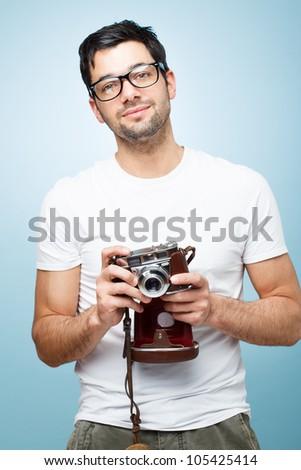 Hipster fashion photographer man holding retro camera - stock photo
