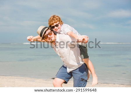 Hipster father with beard and red haired son having great happy time at a summer day. Vacation, happy and friendly family, holidays concept
