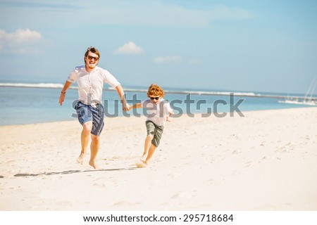 Hipster father with beard and red haired son having great happy time at a summer day. Vacation, happy and friendly family, holidays concept - stock photo