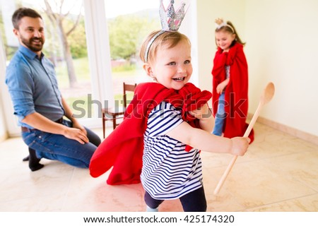 Hipster father with his princess daughters wearing red capes. Young father is enjoying time with his child. Father and daughter at home. Handsome father with little girl. Happy father and daughter. - stock photo
