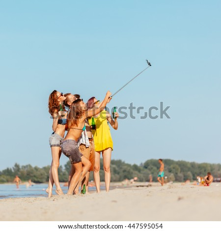 Hipster Friends At The Beach Taking Selfie Using Smart Phone And Monopod