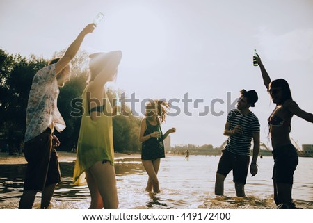 Hipster Friends Dancing At River Shallow And Having Fun - stock photo