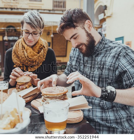 Hipster Friends In Fast Food Reastaurant Eating Burgers. View From Above - stock photo