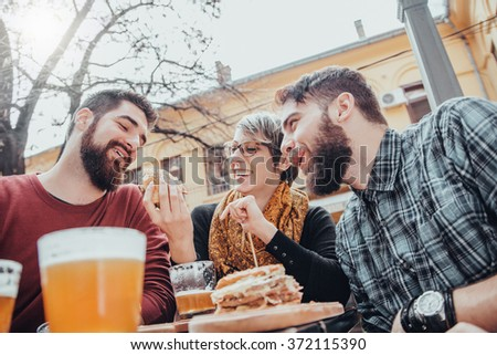 Hipster Friends In Fast Food Restaurant Eating Burgers. - stock photo