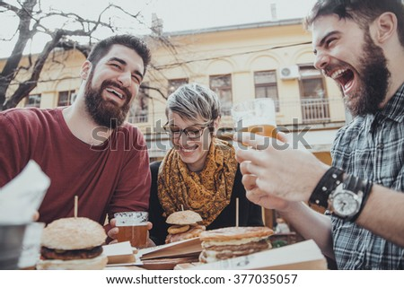 Hipster Friends In Fast Food Restaurant Eating Burgers