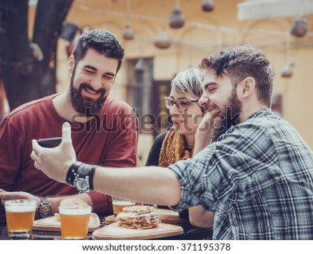 Hipster Friends In Fast Food Restaurant Taking Selfie - stock photo