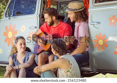 Hipster friends sitting by their camper van on a summers day - stock photo