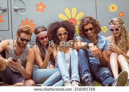 Hipster friends using their phones on a summers day - stock photo