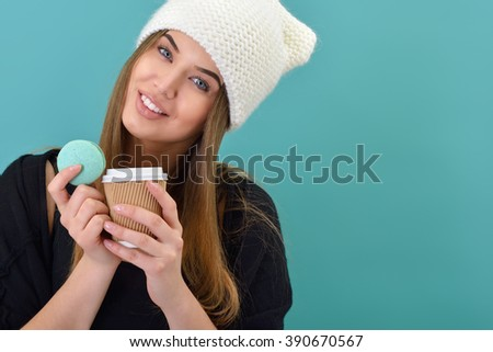 Hipster girl eating french macaron and coffee over turquoise background. Studio female portrait. Diet, sweets, cakes, eating.