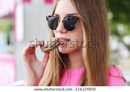 Hipster girl in a cafe eating macaroon. Photo toned style Instagram filters - stock photo