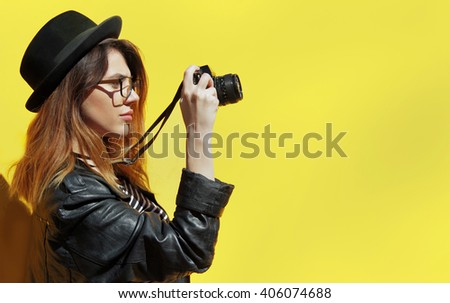 Hipster girl in black hat and eyeglass with look into the old camera.Leather Jacket and jeans shirt clothed.Red haired.Yellow background. - stock photo