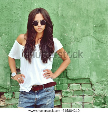 Hipster girl in casual clothes wearing sunglasses posing over green wall - stock photo