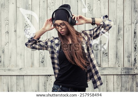 Hipster girl in glasses, headphones and black beanie on the wooden background
