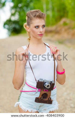 Hipster girl in shorts and a t-shirt with a vintage camera. modern hipster girl photographed using vintage camera. Outdoors lifestyle - stock photo