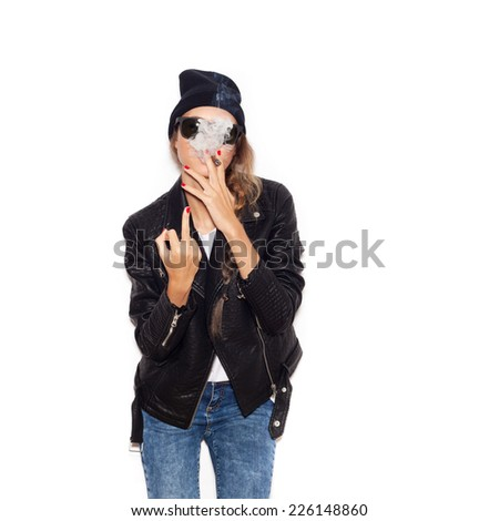Hipster girl in sunglasses and black beanie smoking and showing middle finger over white background, not isolated - stock photo
