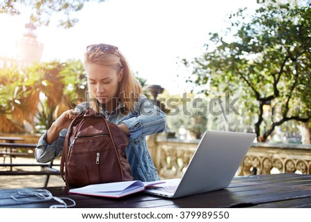 Hipster girl looking for something in the bag while sitting outdoors at the table with open net-book, young female searching the pen in rucksack for writing an essay on a notebook from laptop computer - stock photo