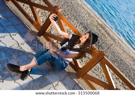Hipster girl making self portrait with her smart phone digital camera while enjoying summer day outdoors, female in fashionable clothes posing while photographing herself for social network picture