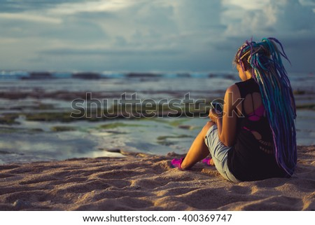 hipster girl on the beach watching the sunset , and calls on the phone, listening to music from the phone.