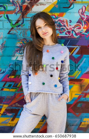 Hipster  girl posing over wall,street style, sport,happy and positive girl,glam rock style,,natural long hair,beauty model face