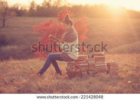 Hipster girl reading at sunset - stock photo