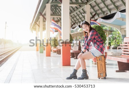 Hipster girl setting on leather vintage bag at railway station, concept travel and leisure