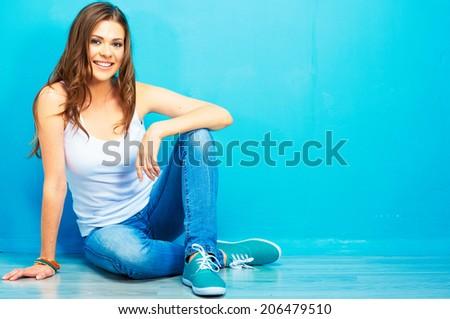 Hipster girl sitting on floor against blue background. - stock photo