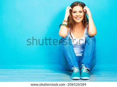 Hipster girl sitting on floor against blue background. - stock photo