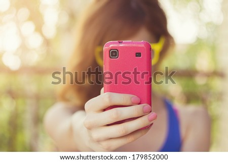 Hipster Girl taking a photo with her pink cell phone - stock photo