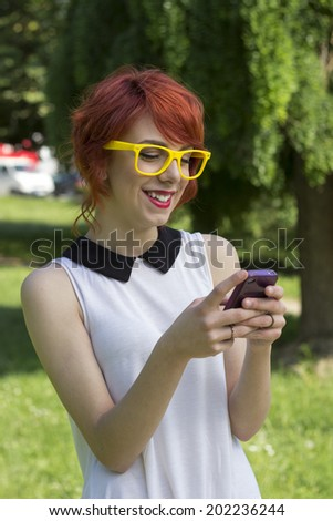 Hipster girl text messaging on her smart phone  - stock photo