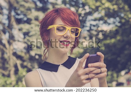 Hipster girl text messaging on her smart phone, toned image, retro colors