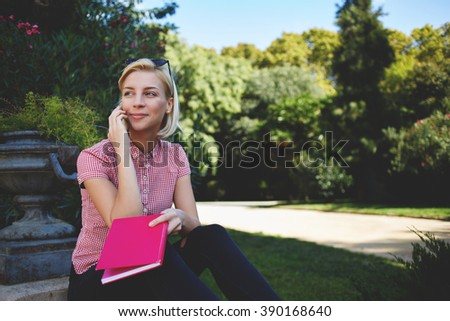 Hipster girl with good mood is calling via cell telephone while sitting in the fresh air in warm spring day, gorgeous female is talking with her friend via mobile phone while resting in park outdoors - stock photo