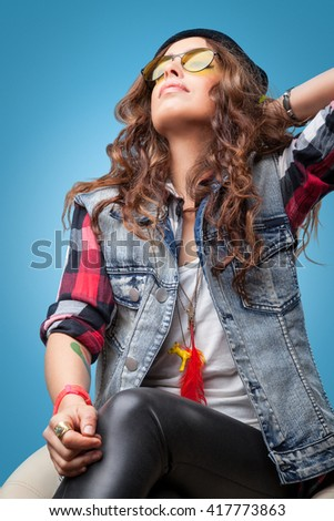 Hipster girl with long hair seating on chair in red checkered shirt,denim vest, glasses and black beanie hat posing looking up with hand up.Closeup portrait on blue background.Youth style fashion