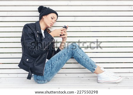 Hipster girl with phone writing text on a white bench in the park.  Outdoors lifestyle portrait of young woman - stock photo
