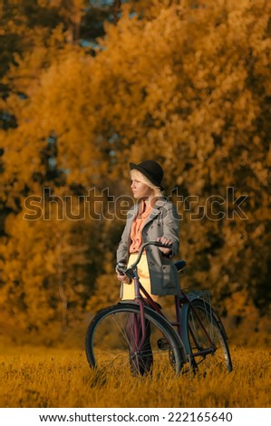 Hipster girl with retro bike on the autumn field  - stock photo