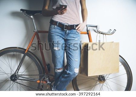 Hipster girl with vintage orange bicycle using modern smart phone, mock-up of blank paper package, brown template shopping bag with handles - stock photo