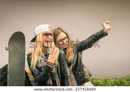 Hipster girlfriends taking a selfie in urban city context - Concept of friendship and fun with new trends and technology - Best friends eternalizing the moment with modern smartphone - stock photo